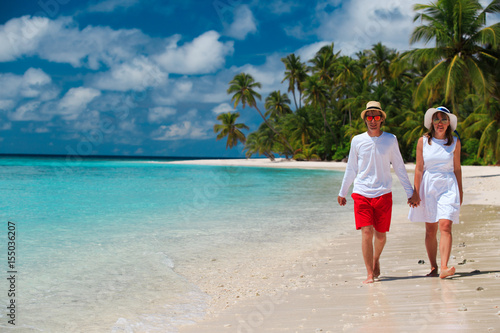 happy loving couple walking on beach Poster
