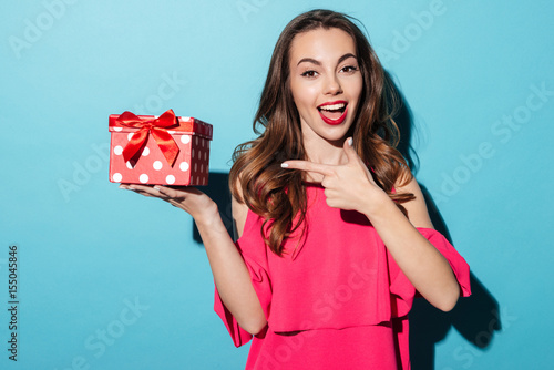 Poster Smiling girl in dress pointing finger at a gift box