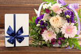 Blue gift box with beautiful bouquet of flowers