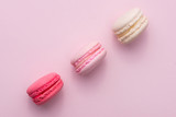 Tasty pink cake macaron or macaroon on pink background from above