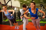 Personal trainer assisting young woman while exercising with suspension in the gym - 155098253