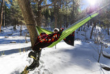 Woman sitting in a hammock with a blanket on a snowy day - 155105810