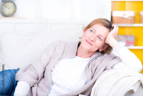 Poster frau mittleren alters liegt auf dem sofa