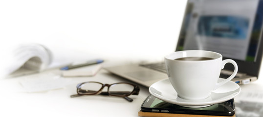 Coffee cup on an office desk with cell phone, laptop, glasses and papers, blurred background fades to white, panoramic banner for web page header, copy space © Maren Winter