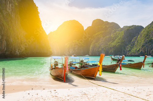 Traditional long tail boat docking in Maya bay in front of a clear and sandy bea Poster