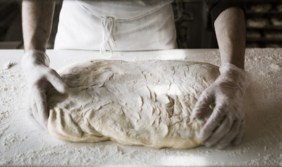 Baker rolling out dough on a counter