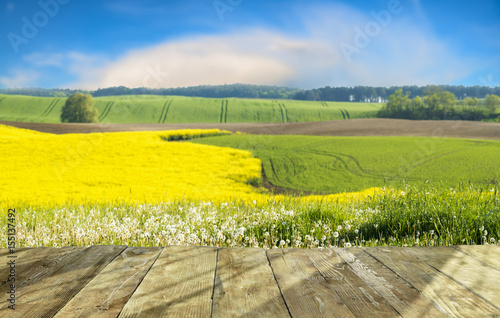 Fotobehang Geel Wooden table with field background