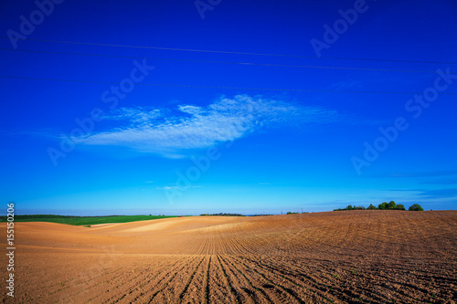 Foto op Aluminium Donkerblauw plowed field and cloudy sky in sunset