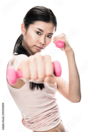 Poster Portrait of young determined woman holding small dumbbells in combat position
