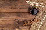 Mat for sushi and chopsticks on wooden background. Top view with copy space