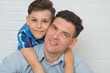 Father holding son on his shoulders, closeup portrait