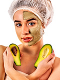Avocado clay face mask. Woman in medical hat holding half of green fruit with stones isolated background. Facial beautiful procedure concept. Cosmetic mask against black dots.