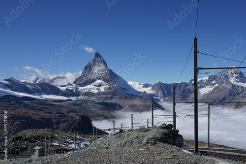 Beautiful iconic mountain Matterhorn with with railway and mist below Zermatt, S Poster