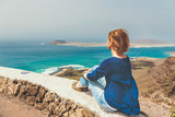 Young woman sitting on stone fence looking at sea - 155212025