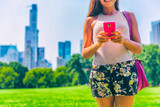New York City lifestyle mobile phone woman texting sms on smartphone. in Central Park, NYC. USA summer travel. - 155322629