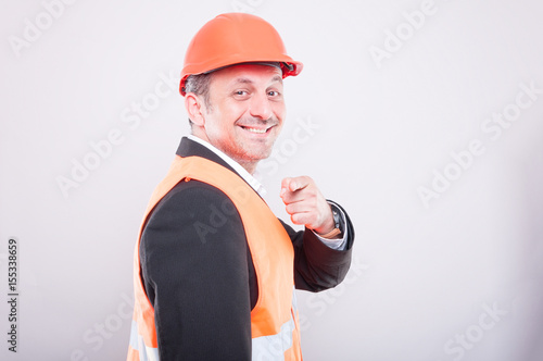 Side view of foreman wearing reflective vest pointing camera