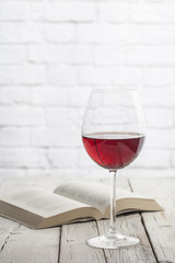 Wine glass and book in a white wooden table