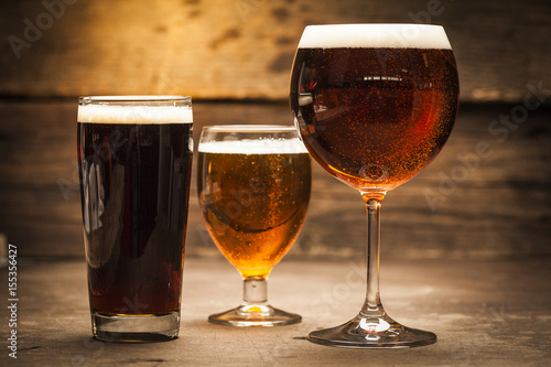 Fototapeta Glasses of beer on a wooden background
