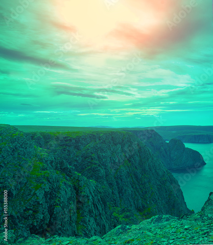 Beautiful rocky seascape with the dramatic cloudy sky at sunset. Wild nature Norway. Islands on the horizon. Nordkapp, Mageroya island, Finnmark