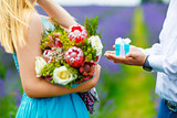 The man's hands stretch out a small gift box with a bow, offering her to marry. She stands in a turquoise dress in the middle of a lavender field, holding a lush bouquet of flowers in her hands - 155400617