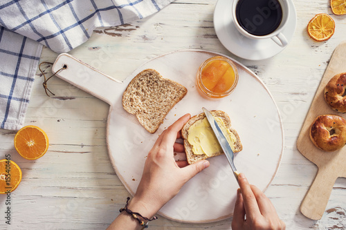 Fototapeta Woman hand spreading butter on sliced bread