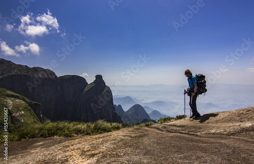 Plakat man with backpack standing on top of mountain with blue sky with clouds