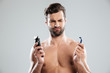 Portrait of a doubtful young man choosing razor