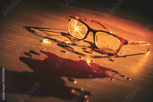 dramatic lit image of broken glasses on the floor with blood © fergregory