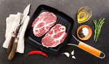 raw steak in a frying pan for the grill on stone background with cutting Cutlery for slicing and spices