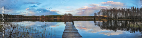 Foto op Aluminium Blauw Panorama landscape. Wooden pier on the lake at sunset, clouds reflection in the water.