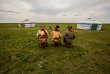 Three Kalmyk musicians in national costumes in the steppe against the background of yurts, the spring steppe