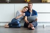 Beautiful young couple using they digital tablet in the kitchen at home. - 155812603