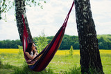 Young lovely brunette in sunglasses is lies in a hammock against the background of the field. - 155848642
