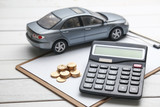 car model,caculator and coins on white table