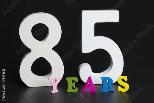 Poster Letters and numbers-eighty-five on the black background.