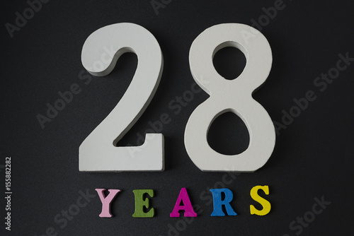 Poster Letters and numbers twenty-eight years on a black background.