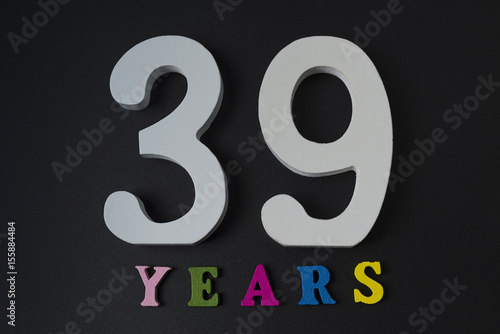 Poster Letters and numbers thirty-nine years on a black background.