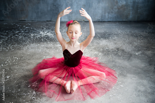 little ballerina sitting on floor, raise hands, close eyes