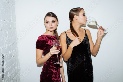 two beautiful girls on white background with glasses of champagne