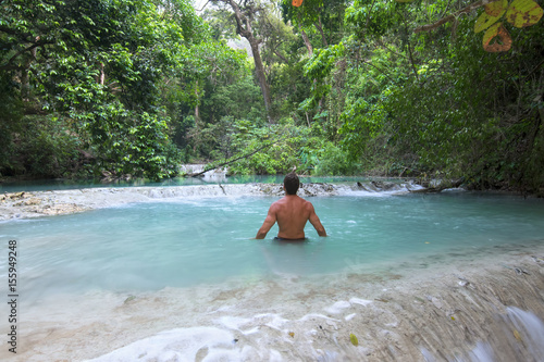 Man wading in tropical paradise pool Poster