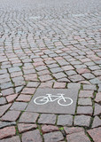 A sign of a bicycle path on a square stone