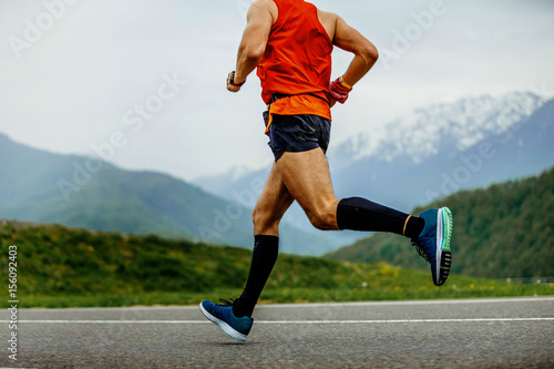 running man athlete compression socks on background mountains and green forest