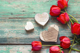 Background with red tulips and wooden hearts on old wooden boards.