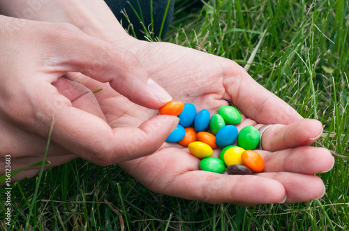 Poster Colorful chocolate candies on hand of pretty girl isolated on grass background