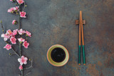 Sushi Set. Small bowl of soy sauce and chopsticks served on stone background. Top view, blank space