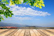 Green leaves and wooden table with blured blue sky background - 156179811