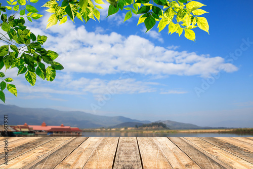 Fotobehang Abstractie Green leaves and wooden table with blured blue sky background
