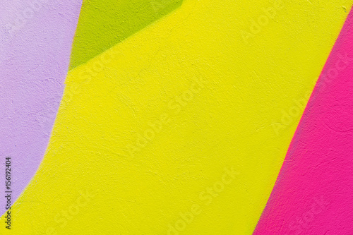 Colorful abstract textured background. Street art, plastered wall facade with green, pink, purple, yellow paints. Colourful grungy surface with place for copy text