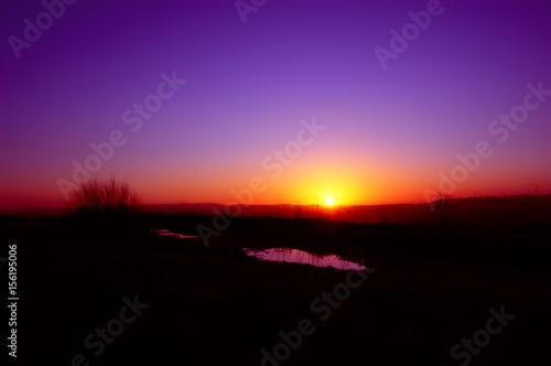 Foto op Canvas Violet Tramonto viola e rosso con sole basso all'orizonte