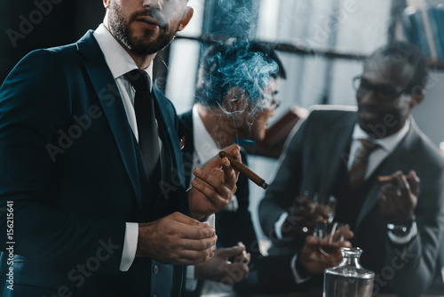 businessman smoking cigar with multicultural business team spending time behind Poster